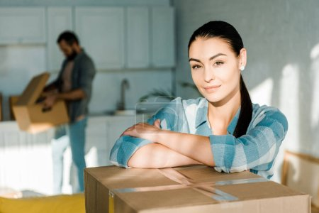 beautiful wife looking at camera on foreground with husband behind packing for new house, moving concept