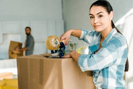 wife packing cardboard box with scotch tape and husband behind, moving concept