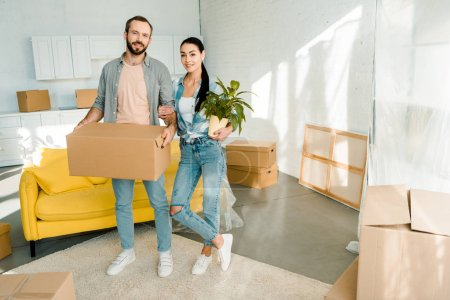 husband carrying cardboard box and wife holding green plant while packing for into new house, moving concept