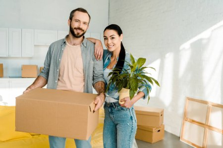 Photo for Husband carrying cardboard box and wife holding green plant while packing for new house, moving concept - Royalty Free Image