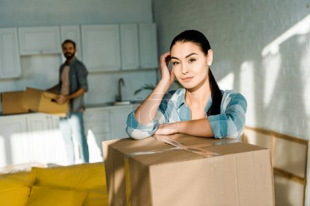 wife leaning on cardboard box with husband packing for new house on background, moving concept