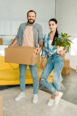 husband carrying cardboard box and wife holding green plant while packing for new house, moving concept