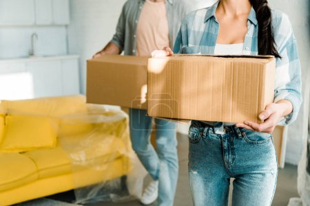 Photo for Cropped view of husband and wife carrying cardboard boxes and packing for new house, moving concept - Royalty Free Image