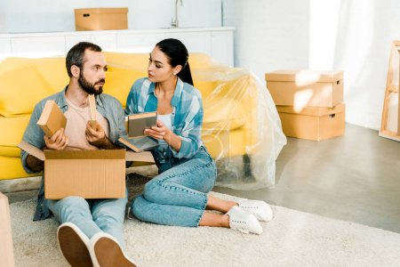 Photo for Serious couple putting books in cardboard box while packing for new house, moving concept - Royalty Free Image