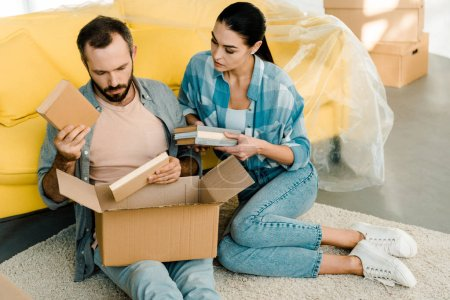 Photo for Beautiful couple putting books in cardboard box while packing for new house, moving concept - Royalty Free Image