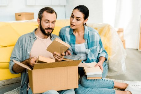 Photo for Couple putting books in cardboard box while packing for new house, moving concept - Royalty Free Image