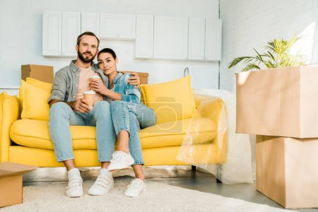 husband and wife sitting on couch and drinking coffee while packing for new house, moving concept