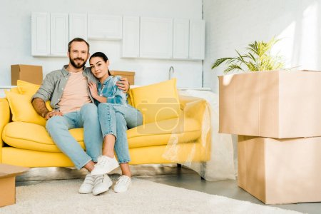 smiling husband and wife embracing and sitting on couch while packing for new house, moving concept