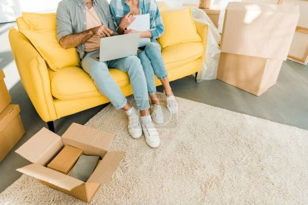 Photo for Cropped view of couple sitting on couch, using laptop and planning relocation to new house, moving concept - Royalty Free Image