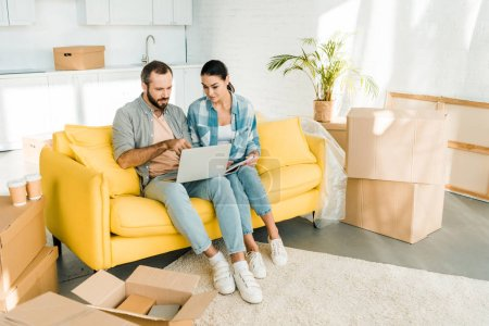 Photo pour Concentré de couple assis sur le canapé, à l'aide d'ordinateur portable et planification de réinstallation à nouveau déménagement, concept - image libre de droit