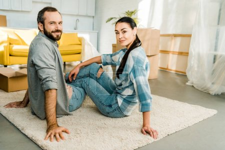 smiling husband and wife sitting on floor and resting after packing for new house, moving concept