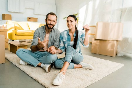 husband pointing finger at wife holding keys from new house, moving concept