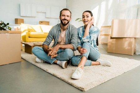 Foto de Marido y mujer sentada en el piso y sonriente después del embalaje para la nueva casa, móvil concepto - Imagen libre de derechos
