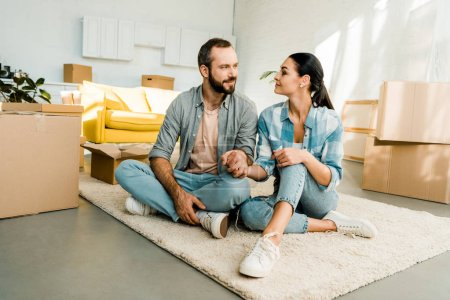husband and wife sitting on floor and holding hands while packing for new house, moving concept
