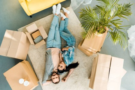 top view of beautiful couple lying on floor and relaxing after packing for new house, moving concept