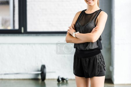 cropped view of smiling sportswoman in black at gym