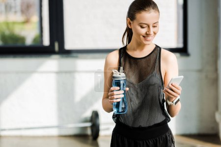 smiling sportswoman holding sport bottle with water and using smartphone at gym