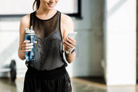 partial view of fit sportswoman holding sport bottle with water and using smartphone at gym