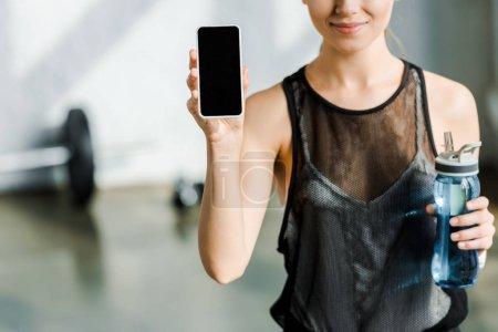 Photo pour Vue recadrée d'une sportive souriante tenant une bouteille de sport et utilisant un smartphone avec écran blanc au centre sportif - image libre de droit
