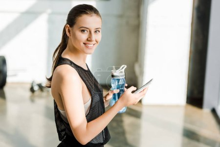 beautiful smiling sportswoman holding sport bottle with water and using smartphone at sports center