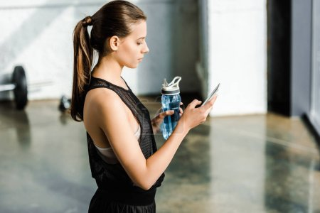 side view of fit sportswoman holding sport bottle with water and using smartphone at gym