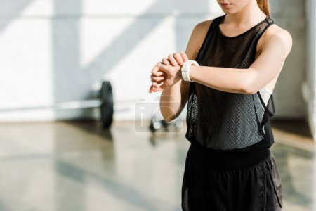 midsection of sportswoman adjusting sport smartwatch at gym