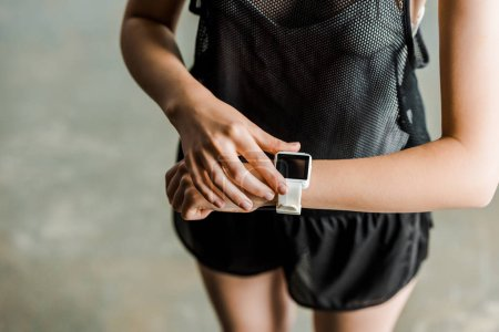 partial view of sportswoman adjusting sport smartwatch with blank screen at gym