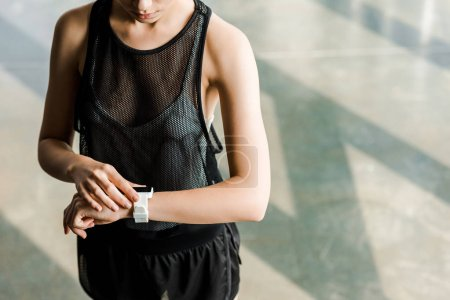 midsection of sportswoman adjusting sport smartwatch on hand at gym