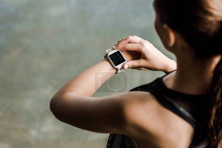 Photo pour Vue recadrée de sportive regardant sport smartwatch avec écran blanc à la salle de gym - image libre de droit