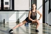 sportive ciblée faisant exercice fente latérale au centre de remise en forme