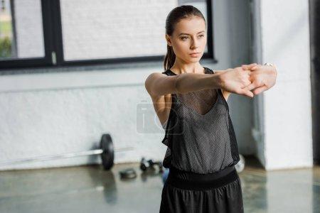 Foto de Hermosa deportista concentrada hacer ejercicio estirar antes de entrenar en el gimnasio - Imagen libre de derechos