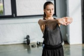 beautiful concentrated sportswoman doing stretching exercise before training session at gym