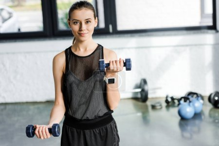 determined smiling sportswoman training with dumbbells at gym
