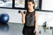 beautiful determined sportswoman training with dumbbells at gym