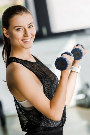 attractive smiling sportswoman looking at camera and training with dumbbells at sports center