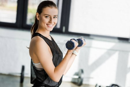 beautiful smiling sportswoman looking at camera and training with dumbbells at sports center