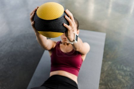 sportswoman on fitness mat training with medicine ball at gym