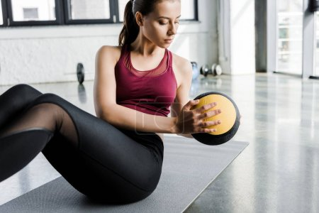 Photo for Focused fit sportswoman working out on abs with medicine ball at sports center - Royalty Free Image