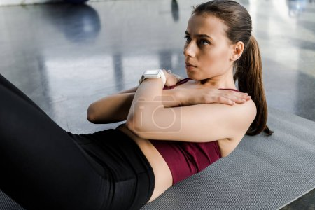 beautiful determined sportswoman doing abs exercise on fitness mat at sports center