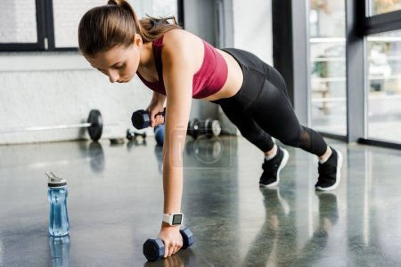 attractive focused sportswoman doing push ups with dumbbells at gym