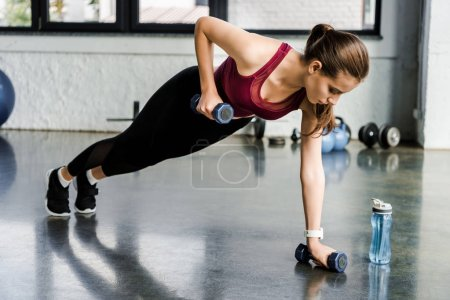 beautiful determined sportswoman doing push ups with dumbbells at gym