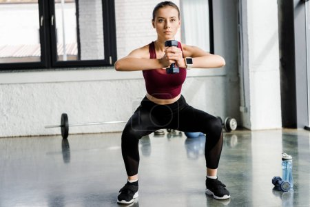 Photo for Determined sportswoman doing squat exercise with dumbbell at sports center - Royalty Free Image