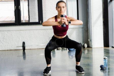 Photo pour Déterminé sportive faisant squat exercice avec haltère au centre sportif - image libre de droit