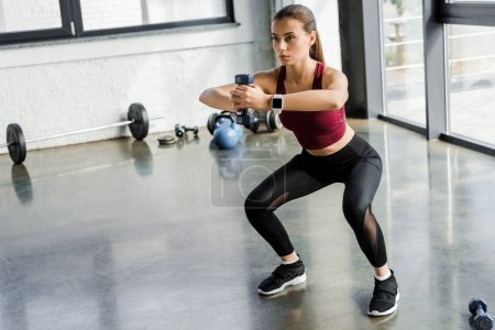 Photo for Focused sportswoman doing squat exercise with dumbbell at sports center - Royalty Free Image