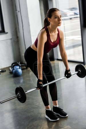 beautiful strong sportswoman in weight lifting gloves training with barbell at sports center