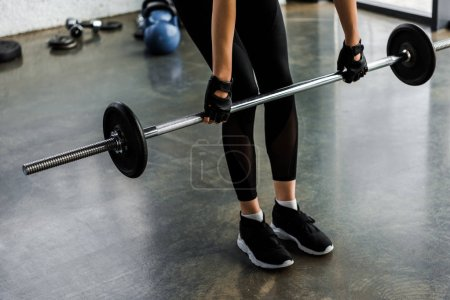 Photo for Low section of sportswoman in weight lifting gloves training with barbell at gym - Royalty Free Image
