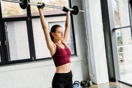 beautiful strong sportswoman in weight lifting gloves training with barbell at gym