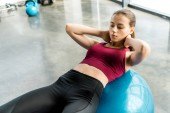 focused sportswoman doing abs exercise on fitness ball at sports center