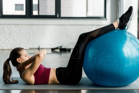 side view of attractive sportswoman doing abs exercise and using fitness ball at gym