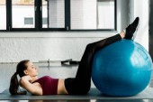 side view of athletic sportswoman doing abs exercise and using fitness ball at gym